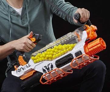 un garçon qui tient un pistolet nerf blanc et orange