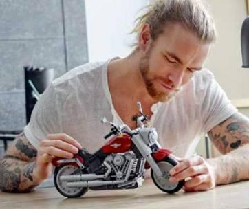 un homme qui joue avec une moto fabriquée en lego