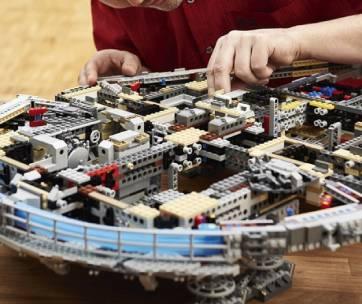 un homme qui farbique un vaisseau en lego