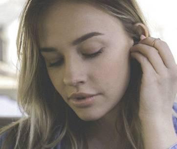 une femme qui mets des bouchons d'oreilles