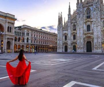une femme en robe rouge devant une église de rome