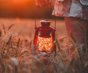 femme tenant une lampe à huile dans un champ de blé