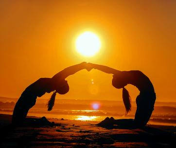 2 femmes qui font du yoga sur la plage au couché du soleil