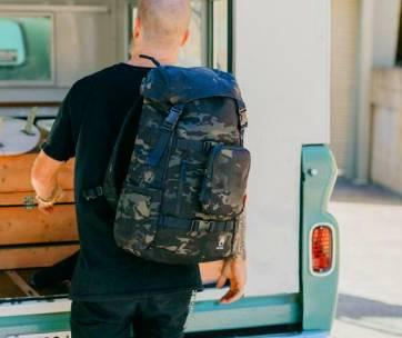 homme portant un sac à dos militaire