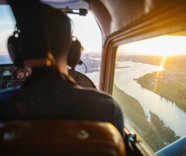 un homme pilote un avion au dessus d'une ville
