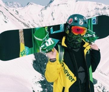 homme tient un snowboard noir dans la neige